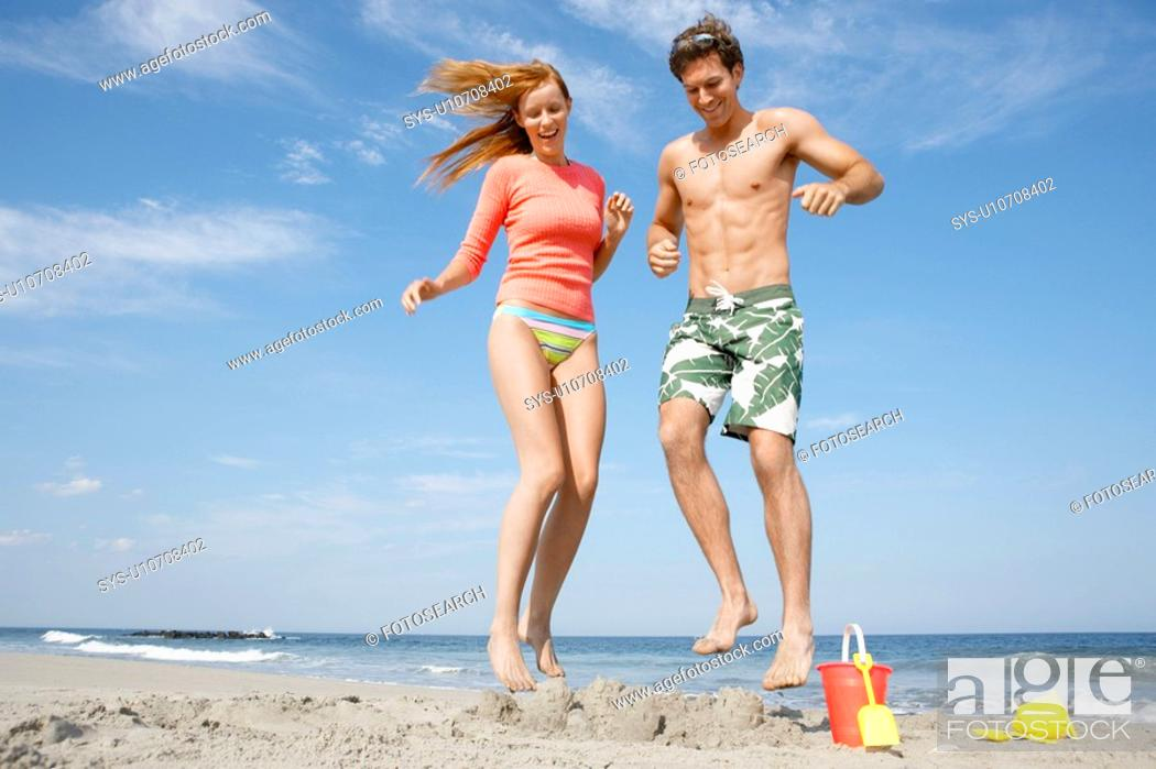 Stock Photo: Young couple jumping on sandcastle.
