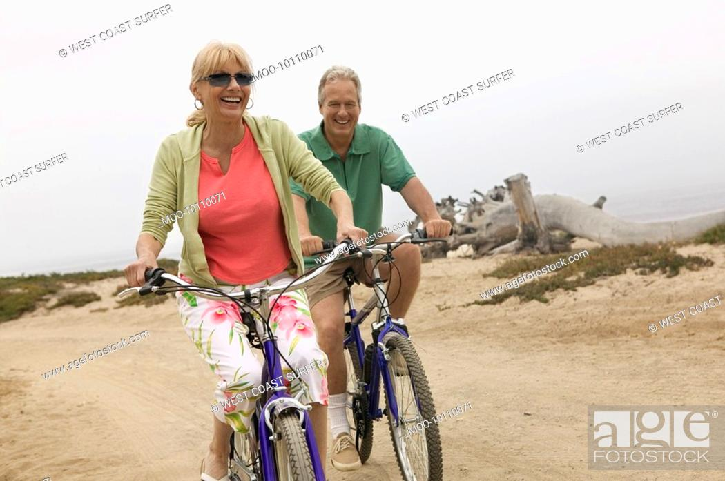 Stock Photo: Couple riding bicycles along beach.