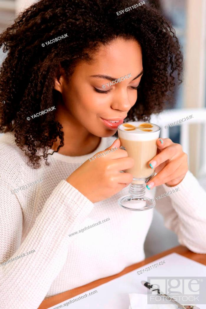 Stock Photo: Appreciating the drink. Young beautiful woman enjoying her cup of latte.