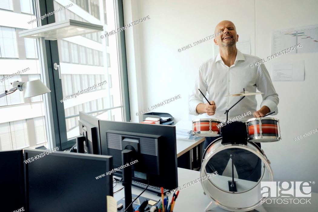 Imagen: Businessman making noise with drums in his office.