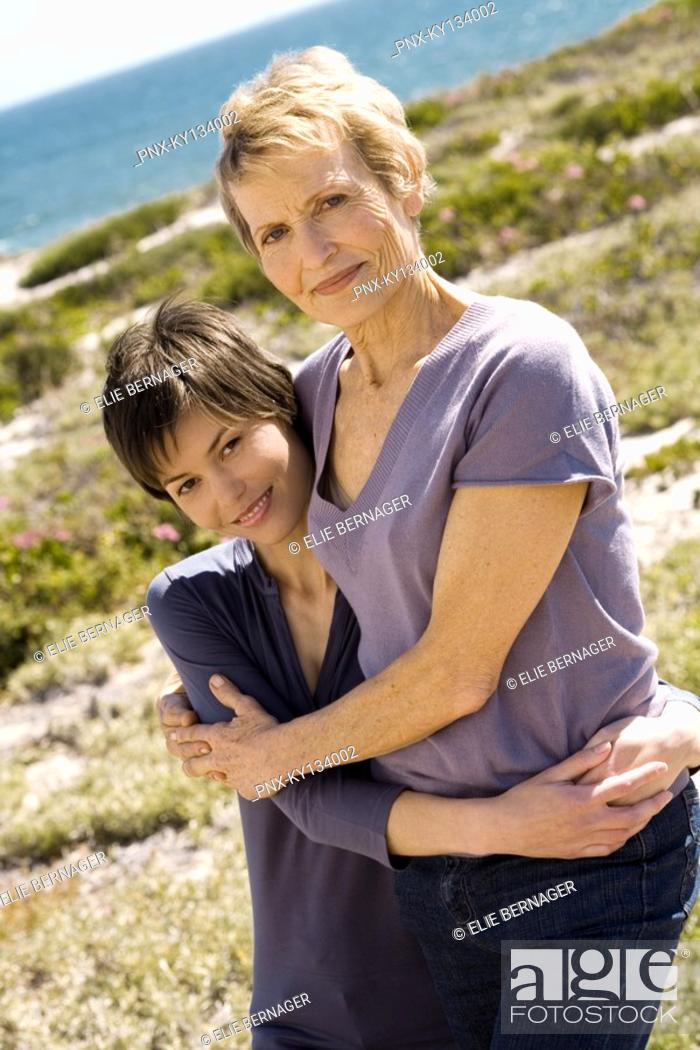 Stock Photo: Senior woman and adult daughter embracing, outdoors.