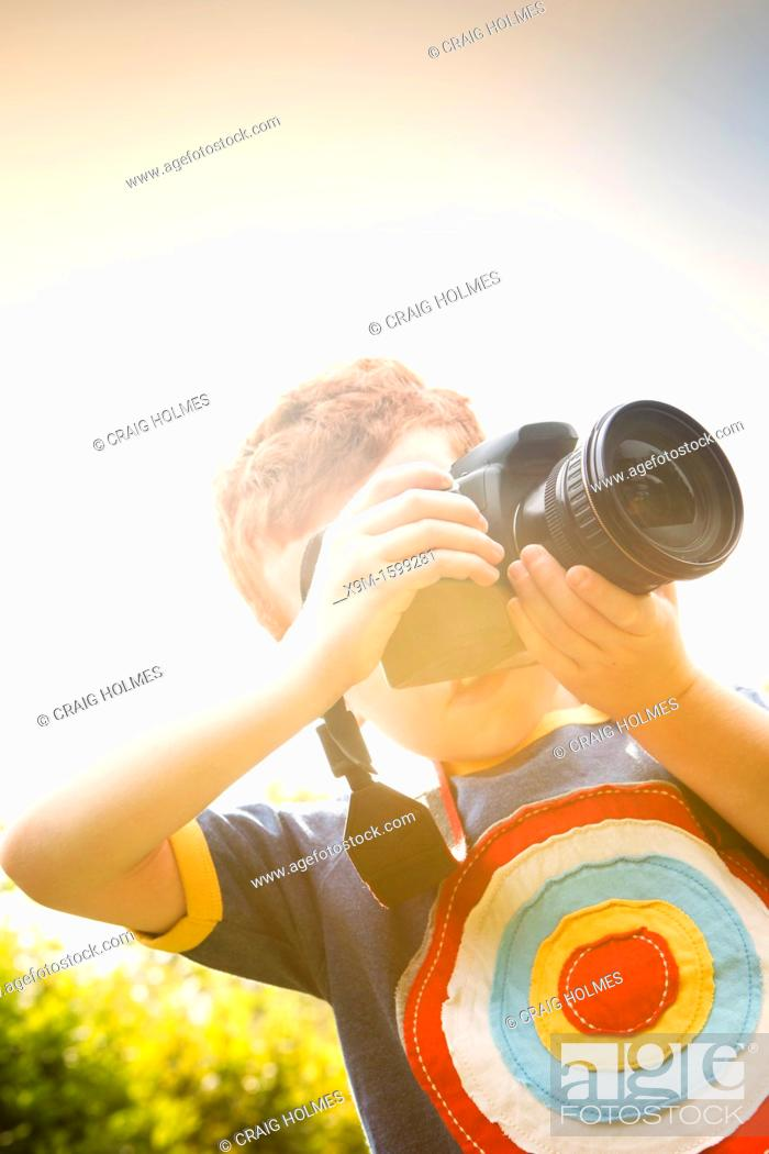Stock Photo: A Young boy, aged 7, using a digital SLR camera in a sunny garden.