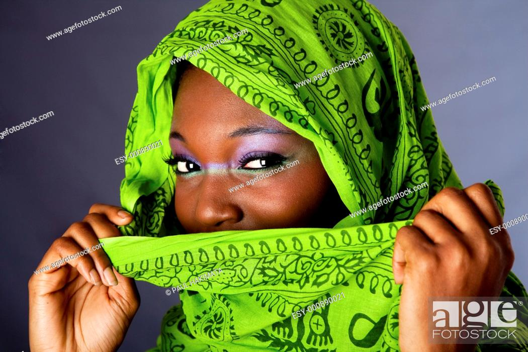 Stock Photo: The face of an innocent beautiful young African-American woman covering her mouth with green headwrap and purple-green makeup, isolated.