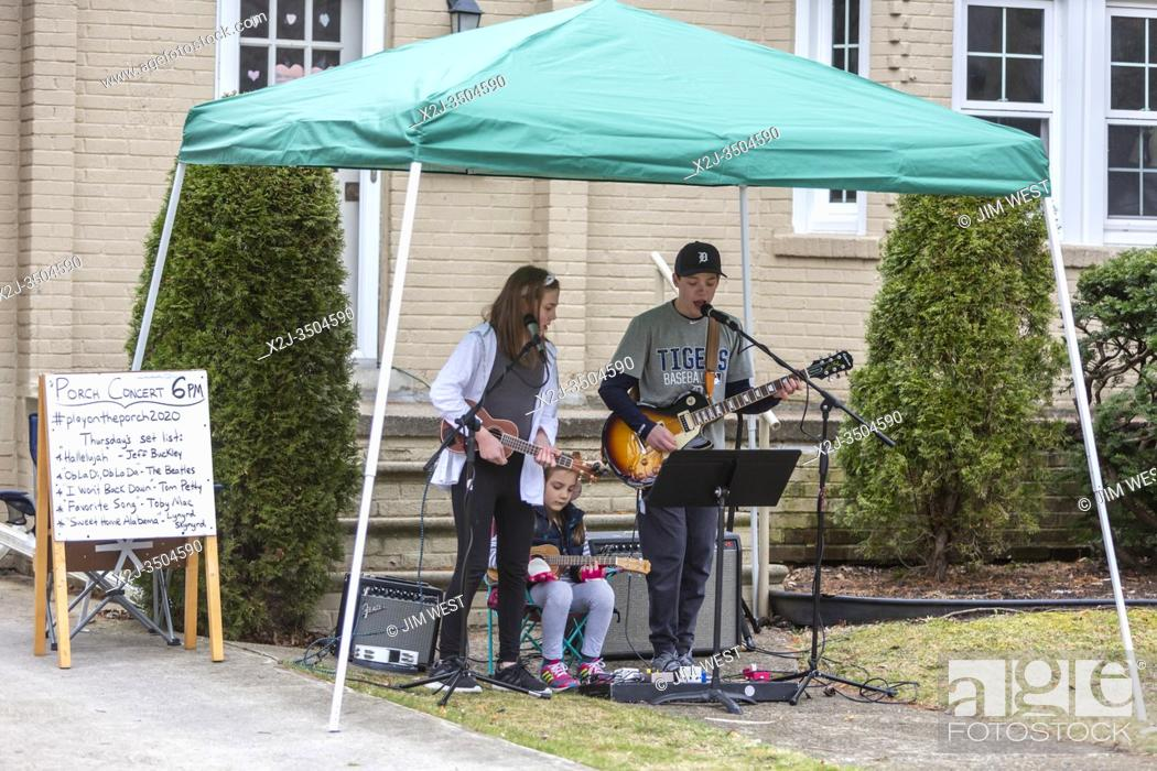 Stock Photo: Grosse Pointe Park, Michigan USA - 26 March 2020 - Nolan Eszes, 14, and his sisters Hadley, 11, and Sidney, 6, play a porch concert for their neighbors.