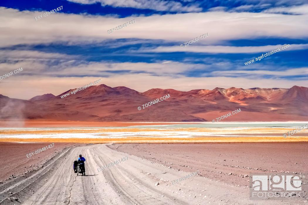 Stock Photo: Woman cyclist struggling and pushing her bike on the sandy corrugated road in Altiplano in Bolivia.