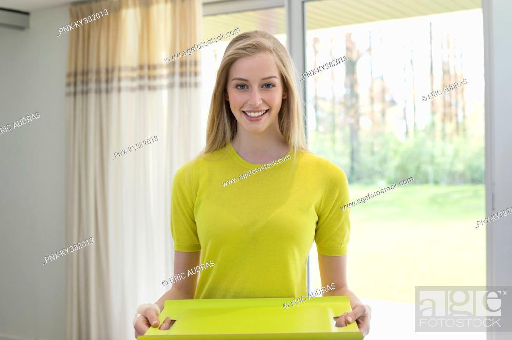 Stock Photo: Happy woman carrying an empty tray.