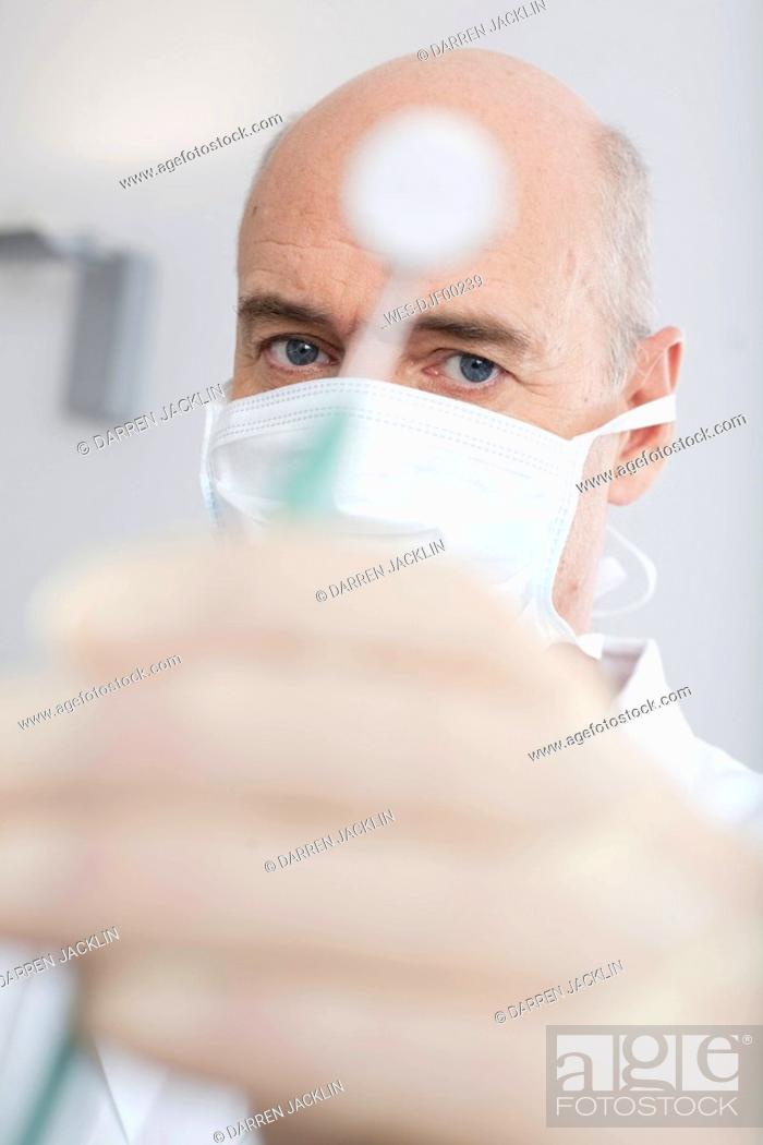 Stock Photo: Germany, Bavaria, Landsberg, Dentist holding mirror, portrait.