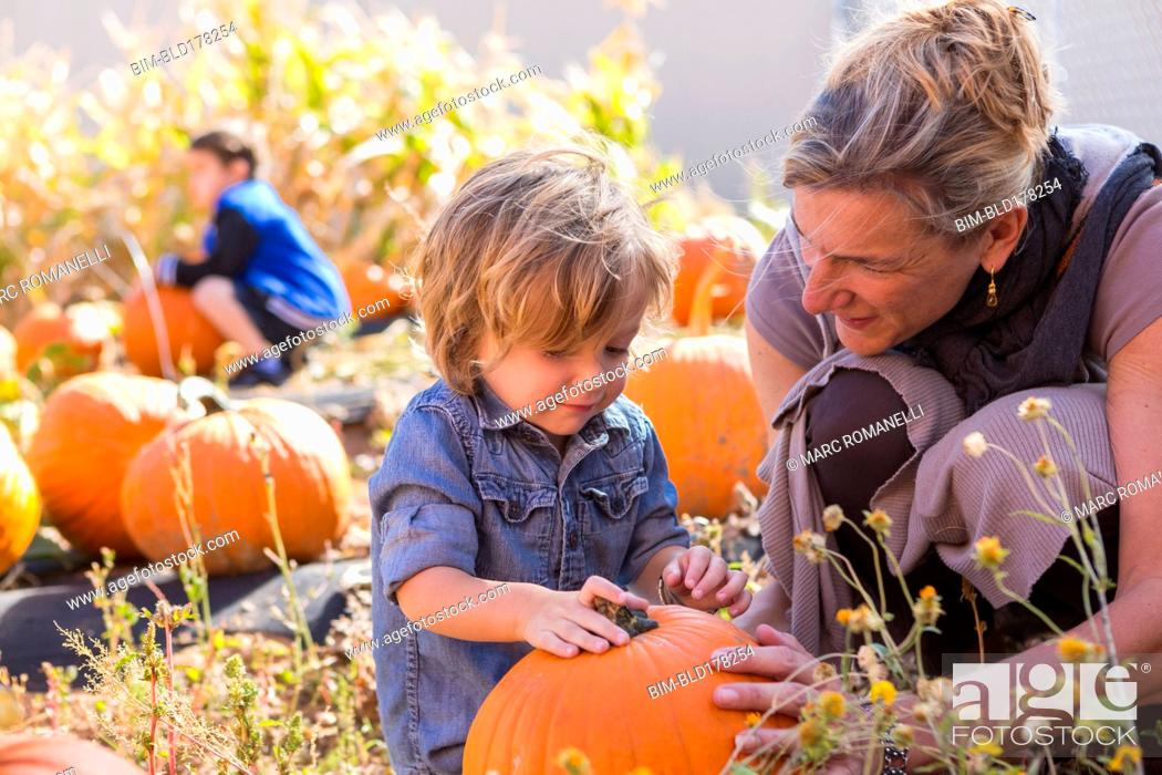 Stock Photo: Caucasian mother and son in pumpkin patch.