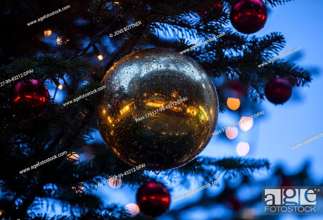 Stock Photo: The market place is reflected in the Christmas ball covered in raindrops after the opening of the Christmas market in Luebeck, Germany, 27 November 2017.