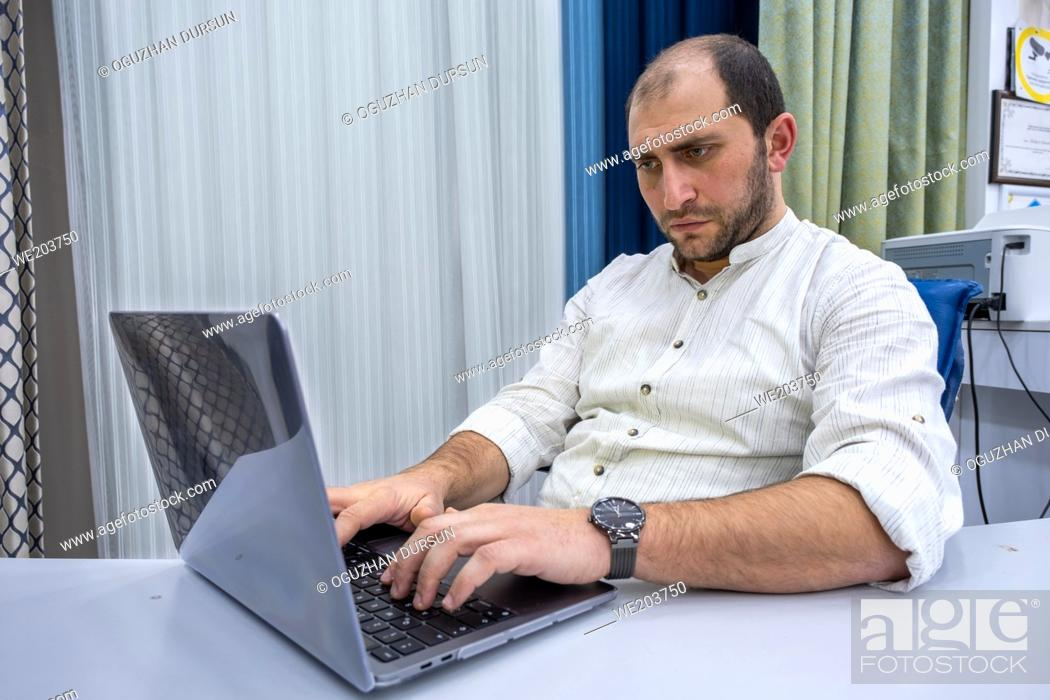 Imagen: a man concentrated typing on his computer while working hardly in his bright office with copy space.