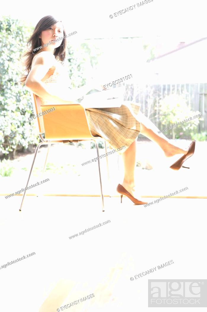 Stock Photo: Woman sitting on chair, side view.