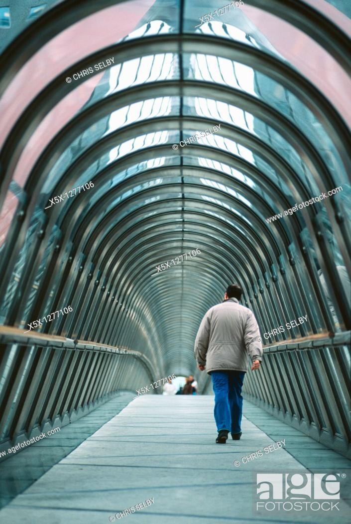 Stock Photo: A man walks alone through the tunnel of a covered skybridge in La Defense, Paris, France.