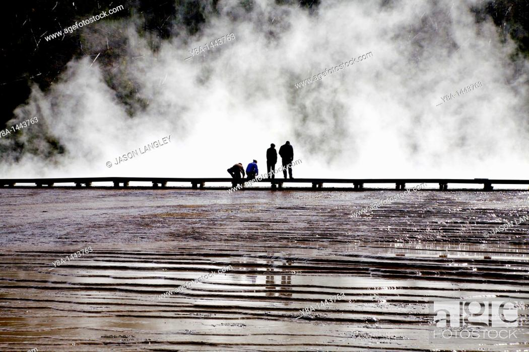 Stock Photo: People standing against a steamy backdrop at Midway Geyser Basin, Yellowstone National Park, Wyoming, United States.