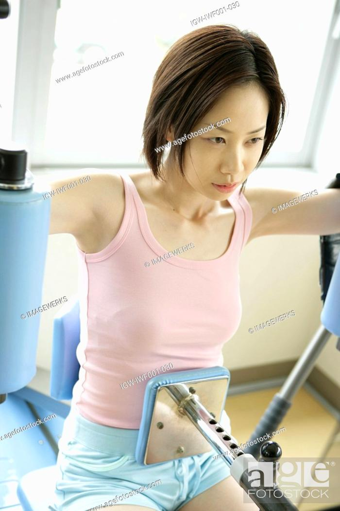 Stock Photo: A young woman exercising for abs and shoulders on the latest equipment in the gym.