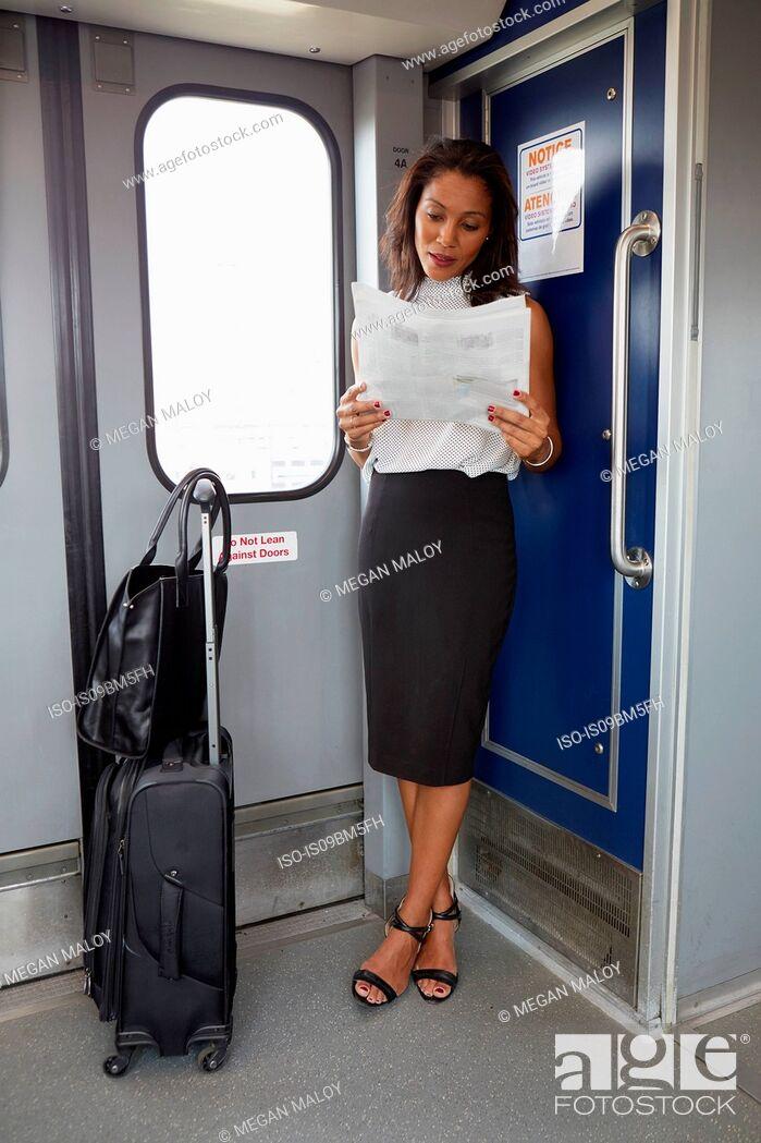 Imagen: Businesswoman reading newspapers on train.