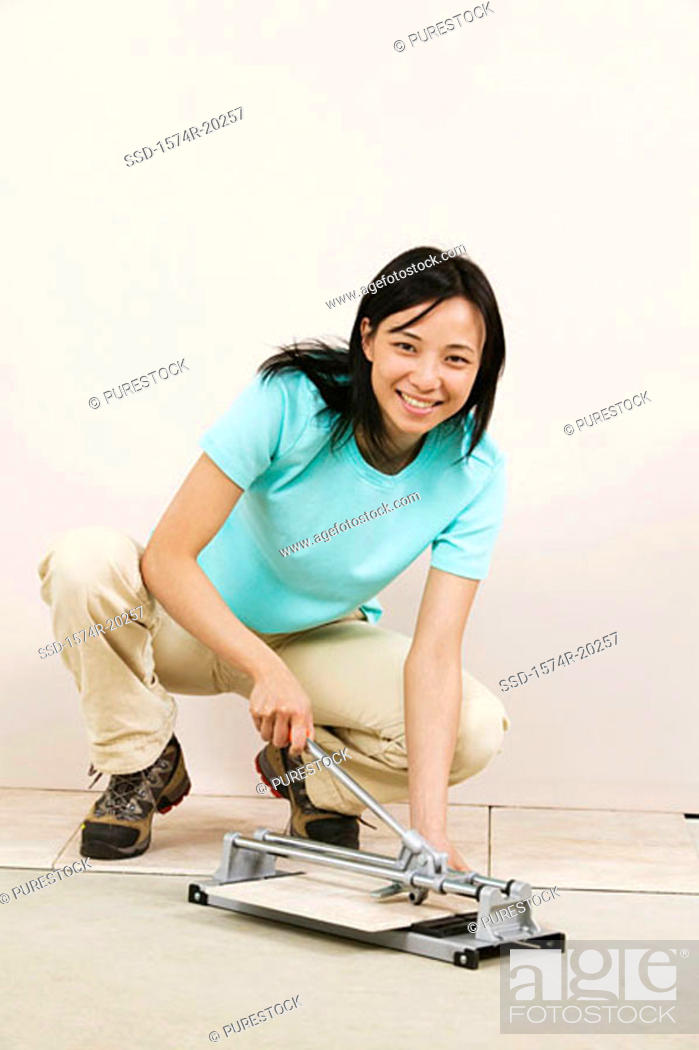 Stock Photo: Portrait of a young woman cutting tile with a tile cutter.