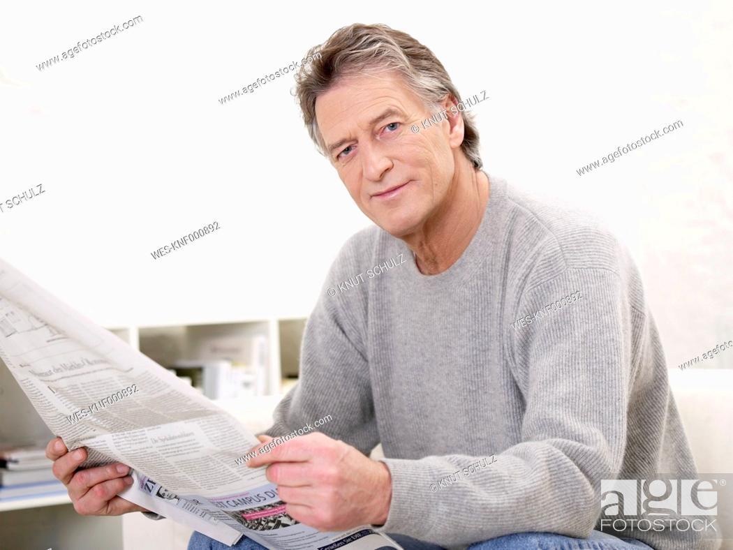 Stock Photo: Germany, Hamburg, Senior man with newspaper, portrait.