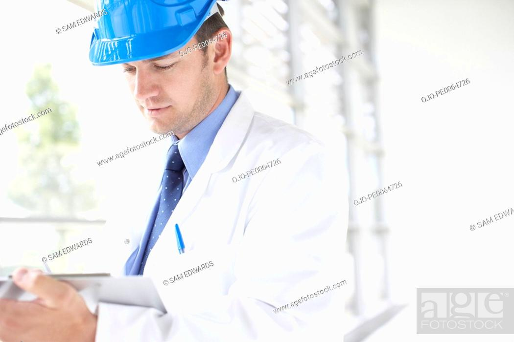 Stock Photo: Businessman in hard-hat writing on clipboard.