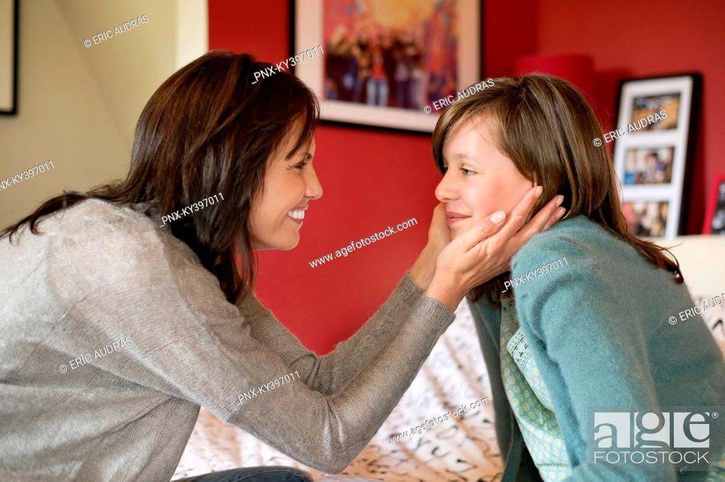 Stock Photo: Woman pampering her daughter in the bedroom.