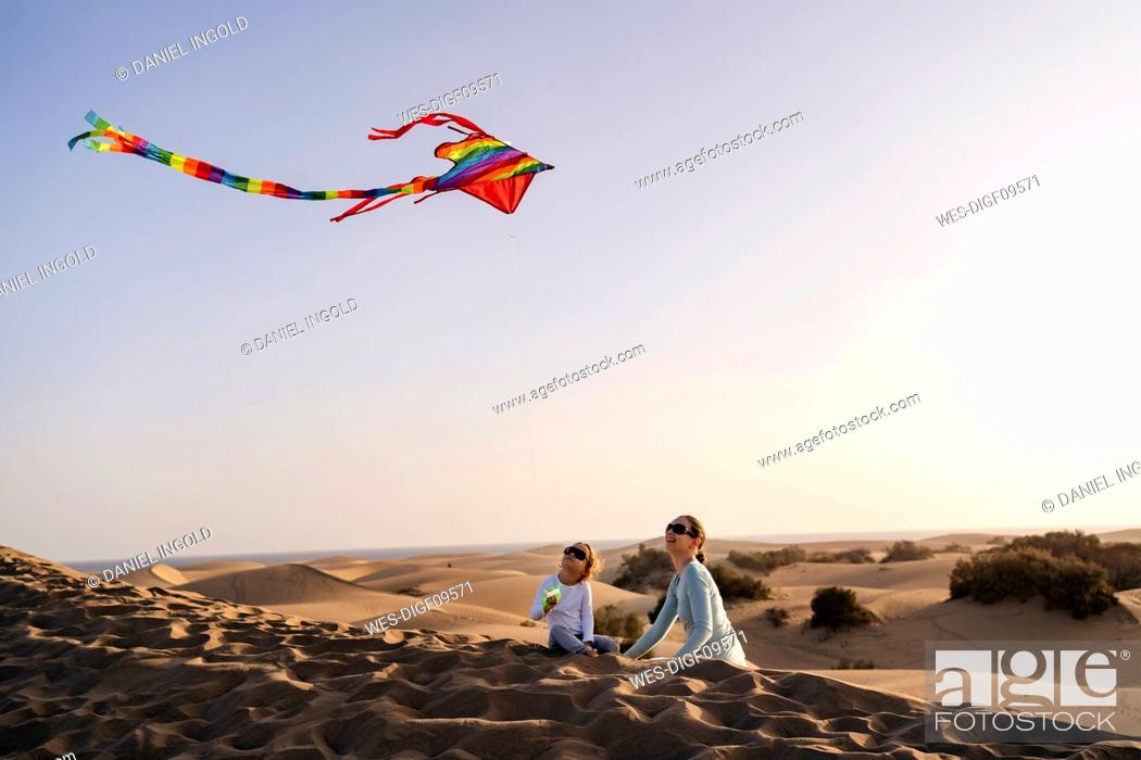 Stock Photo: Mother and daughter flying kite in sand dunes, Gran Canaria, Spain.