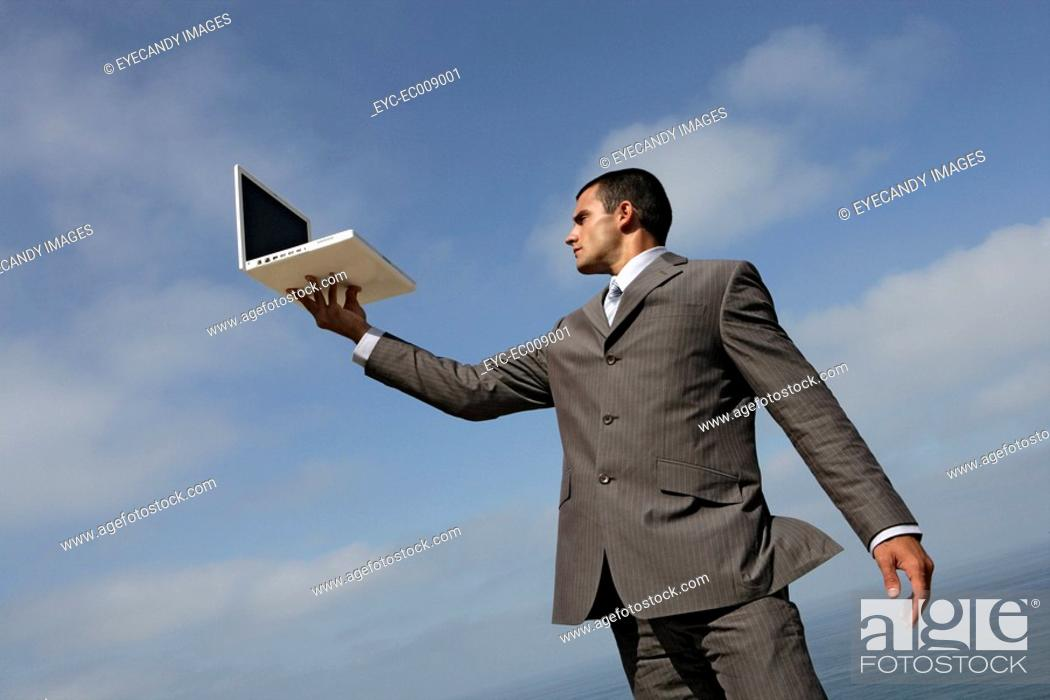 Stock Photo: Suited man holding a laptop.