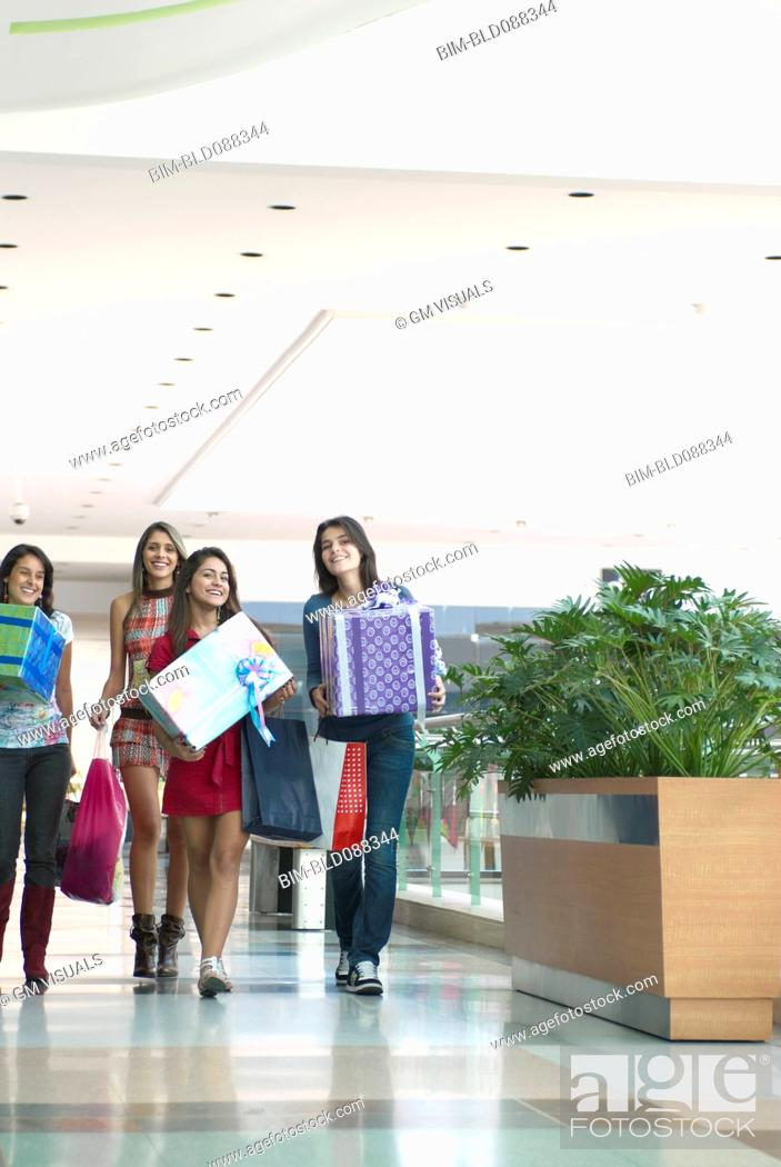Stock Photo: Hispanic friends carrying gifts in shopping mall.