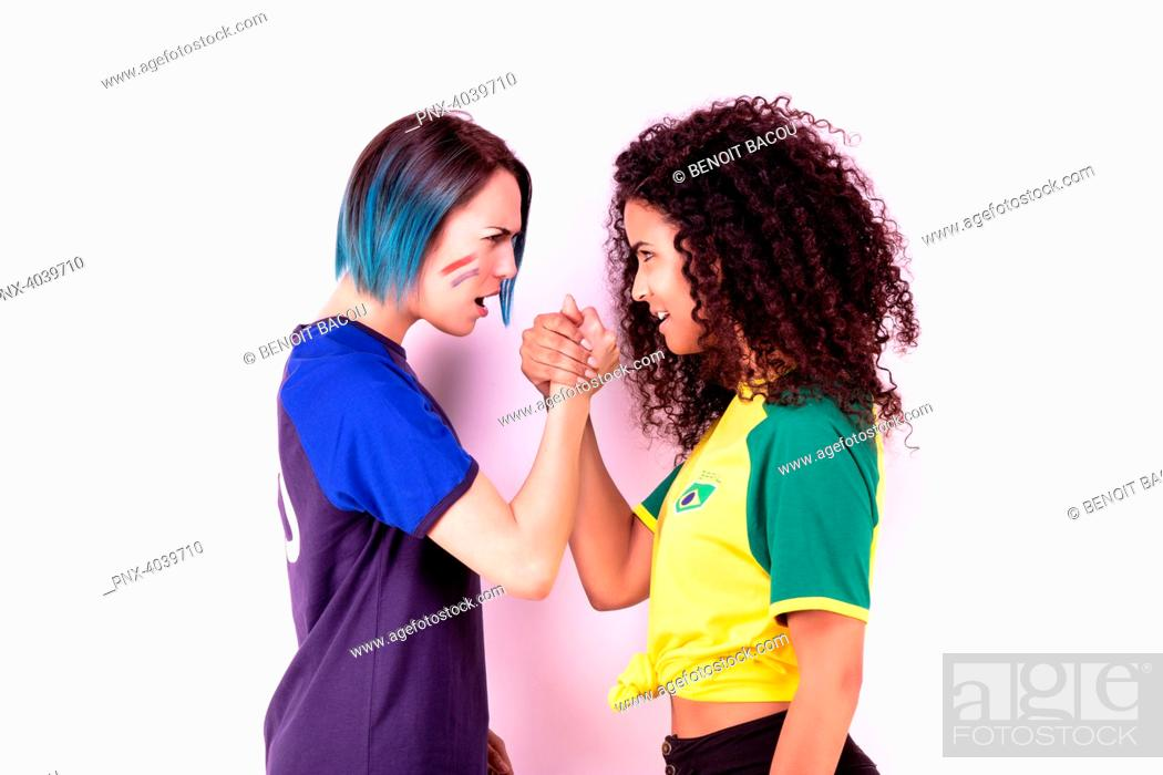 Stock Photo: Arm wrestling of two young fans of the Brazil team and the France team.