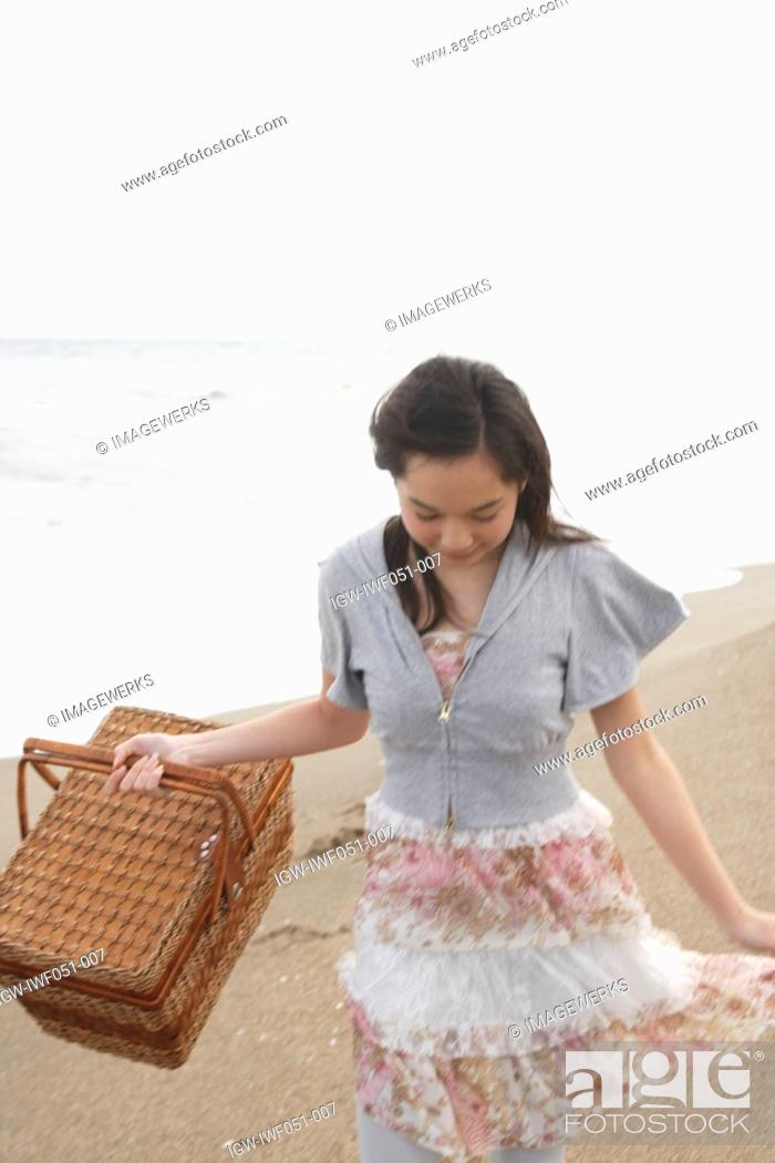 Stock Photo: Teenage girl 14-15 with picnic basket at beach.