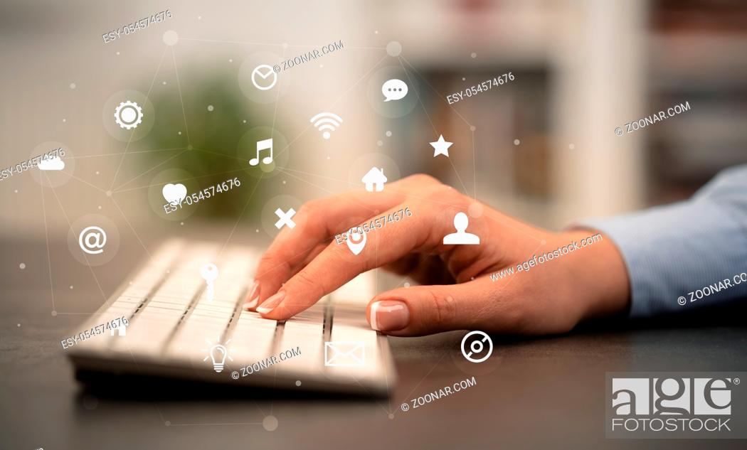 Stock Photo: Business woman hand typing on keyboard with application icons around.