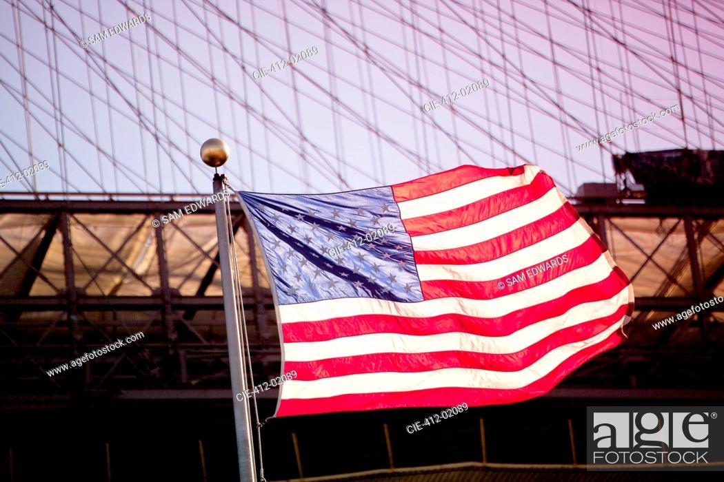 Stock Photo: American flag waving by urban bridge.