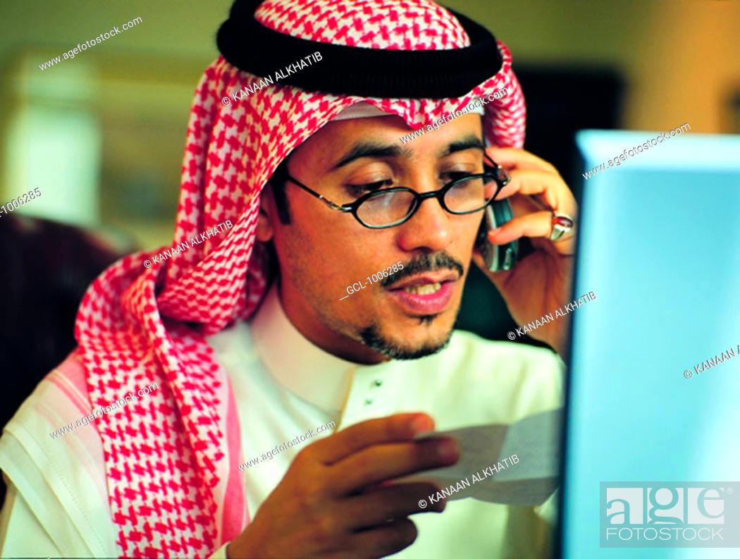 Stock Photo: Saudi businessman using mobile phone and laptop.