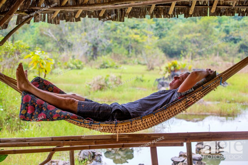 Stock Photo: Tourist relaxes in a bamboo hammock, Vang Vieng, Laos.