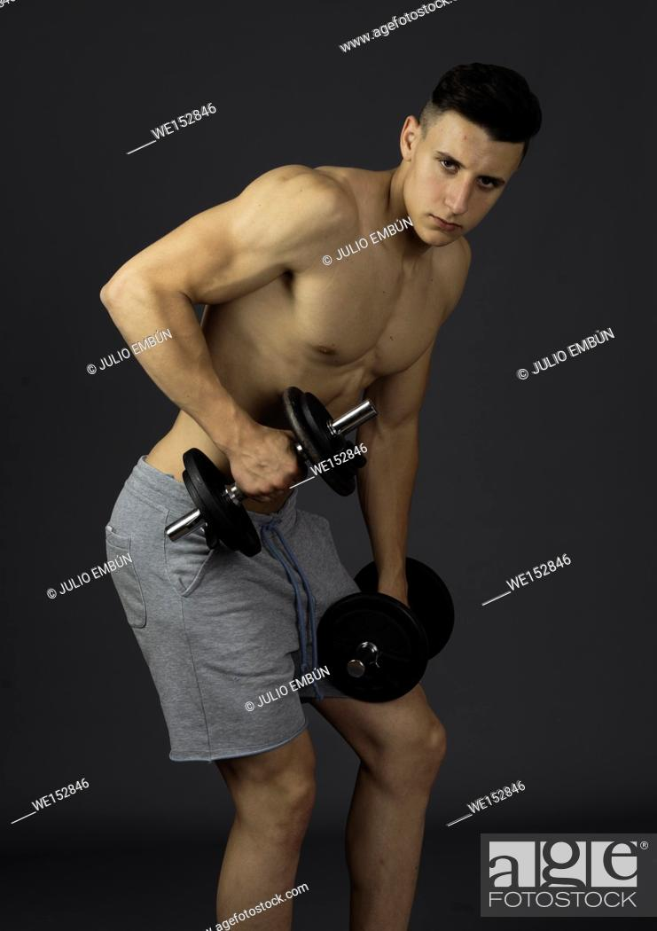 Photo de stock: Young athletic and shirtless boy poses in the studio.