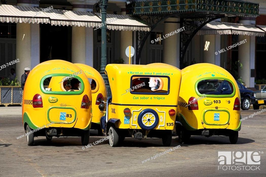 Stock Photo: Several yellow three wheeled taxis parked at a taxi rank, Havana, Cuba.