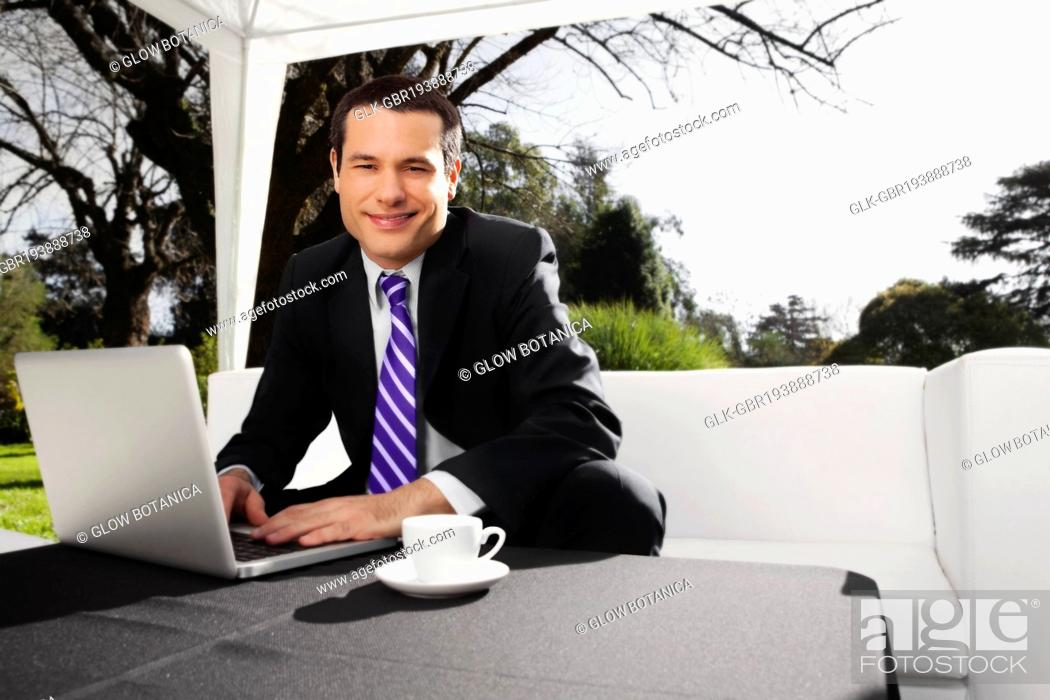 Stock Photo: Businessman using a laptop in a park.