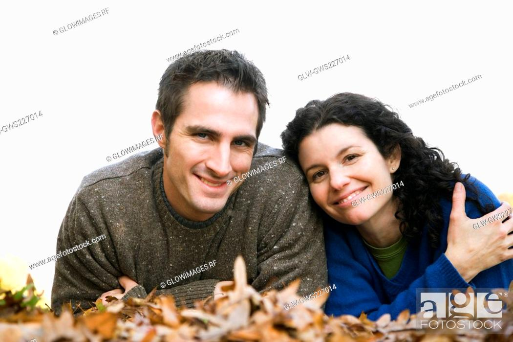 Stock Photo: Portrait of a couple lying in a lawn.
