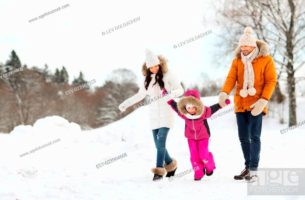 Stock Photo: parenthood, fashion, season and people concept - happy family with child in winter clothes walking outdoors.