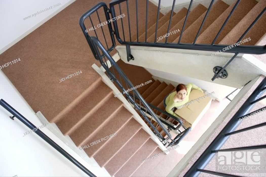 Stock Photo: Woman carrying stacked boxes up staircase.