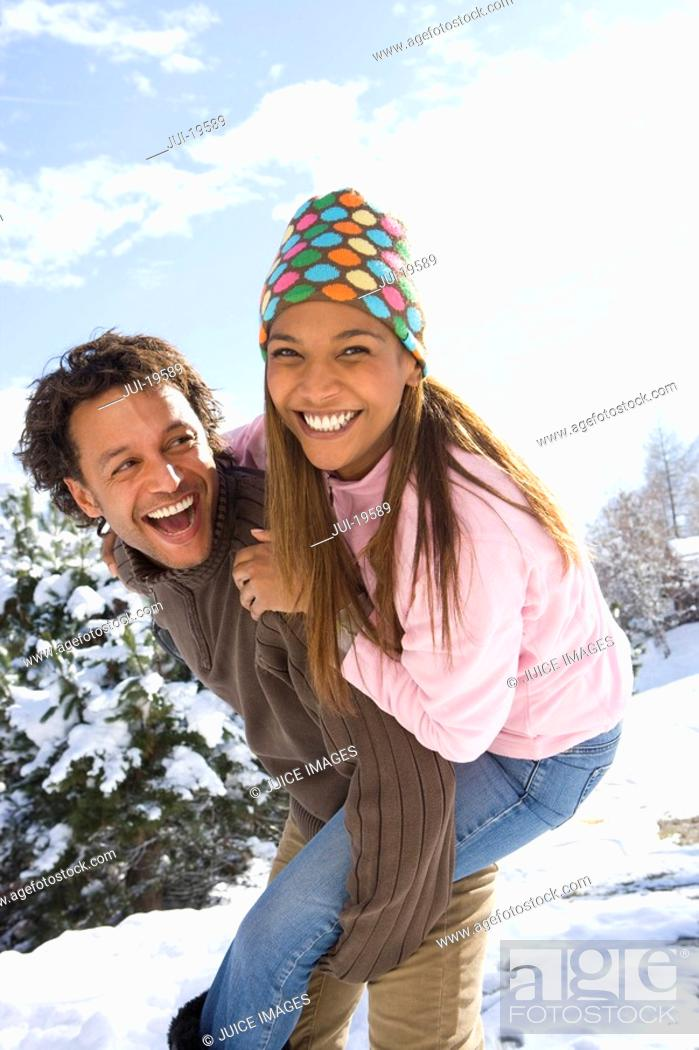 Stock Photo: Portrait of happy mixed race couple in snow.