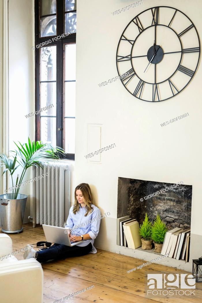 Stock Photo: Woman sitting on the floor at home using laptop.