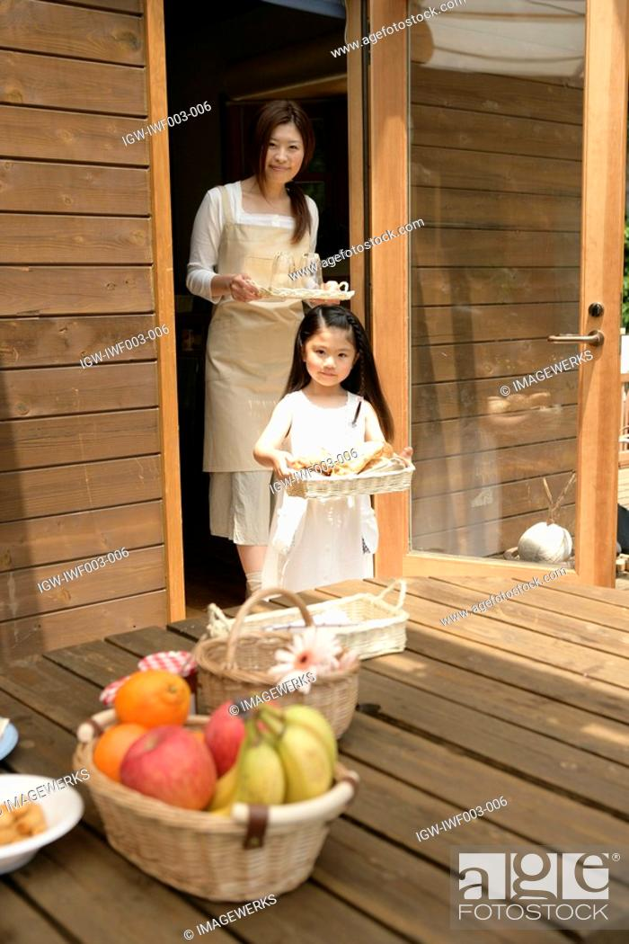 Stock Photo: A small girl helping her mother to place meal on the wooden table.
