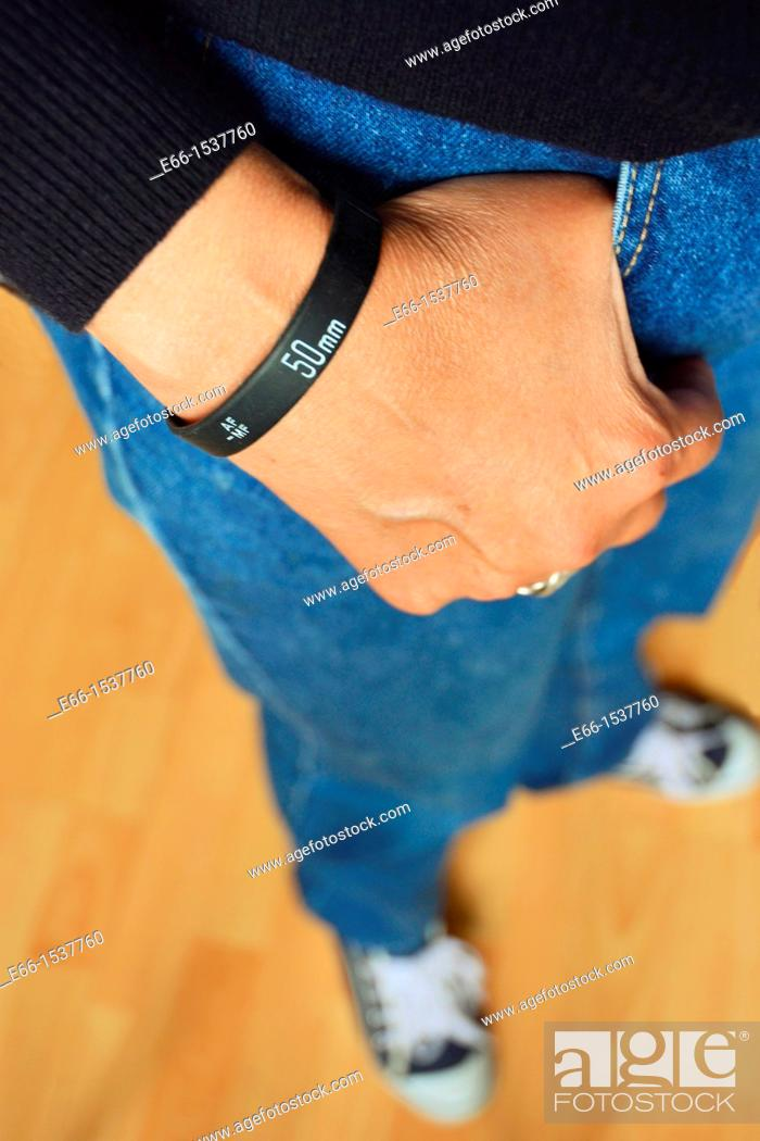 Stock Photo: Woman in blue jeans, black sweater and sneakers, wearing a 'Lens Bracelet' designed by Adam Elmakais - with shallow depth of field.