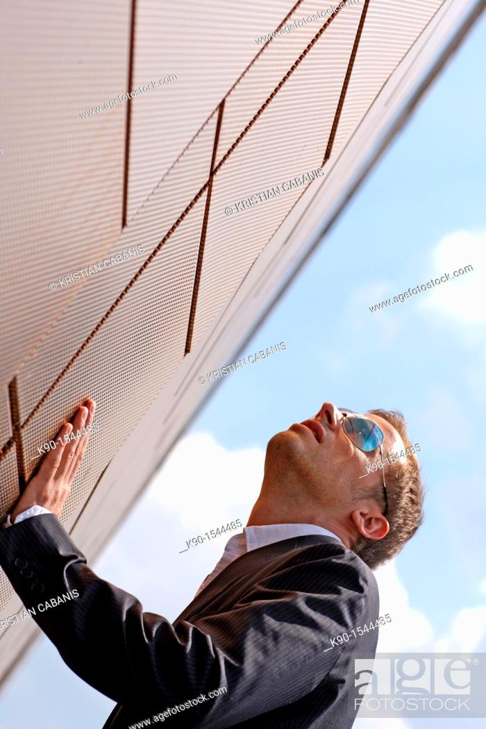 Stock Photo: Brown haired young man with sunglasses, looking up into the air, supporting himself by with one hand at the wall, blue skyl, Hamburg, Germany, Europe.