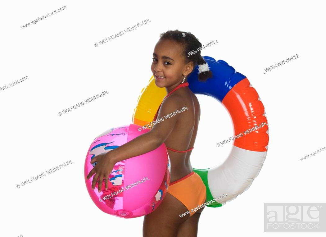 Stock Photo: African girl 6-7 holding floating tire and beach ball, side view, portrait.