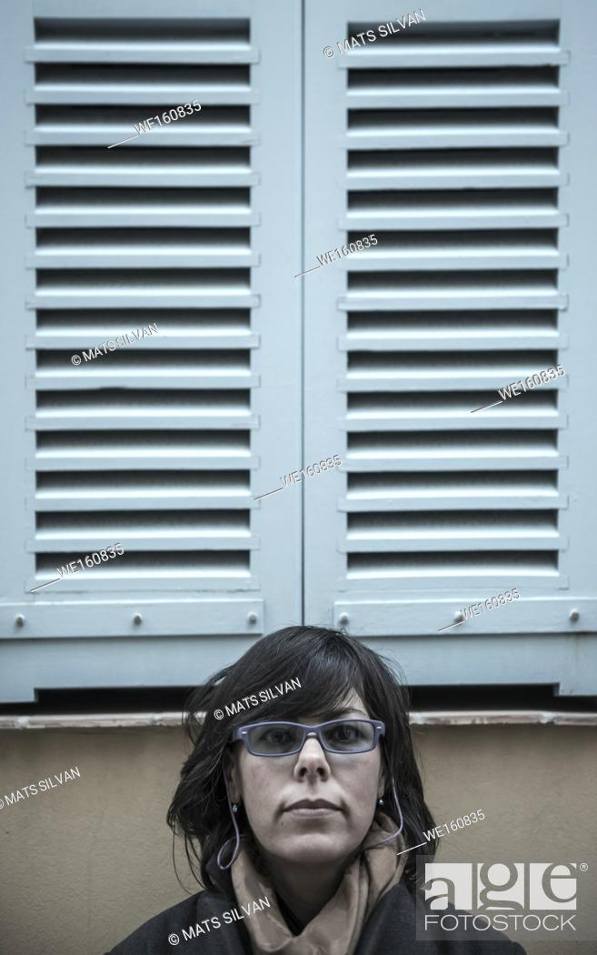 Stock Photo: Woman Under a Window with Shutter in Antibes, France.