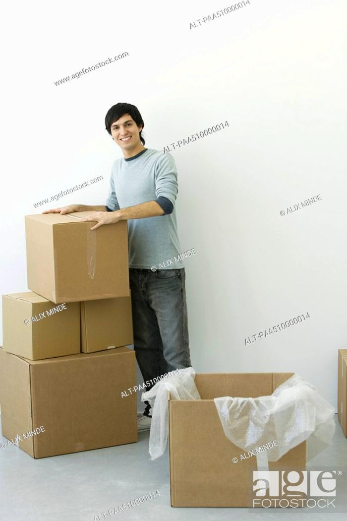Stock Photo: Man standing by stack of cardboard boxes, smiling at camera.