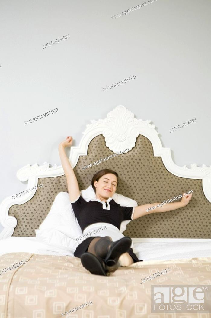 Stock Photo: Maid stretching in bed.