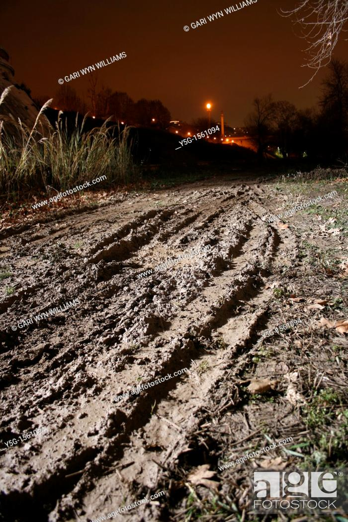 Stock Photo: tyre tracks in field at night.