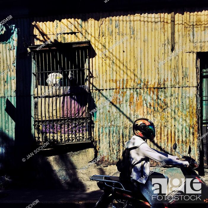Stock Photo: A Salvadoran man rides a motorcycle in front of a low class house, designed by using Spanish colonial architecture elements.