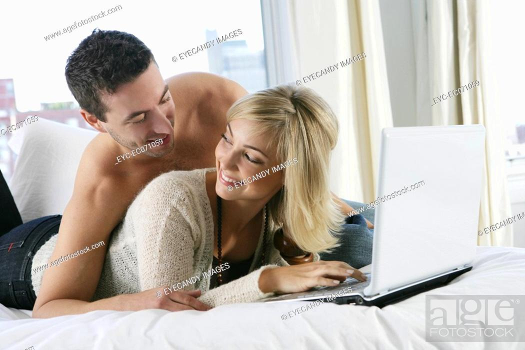 Stock Photo: Young happy couple using laptop in bed.